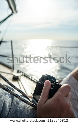 A man with a camera in his hand relaxed sitting on the deck of a yacht, on a blurred background of the sea, sky and sunlight, a warm summer day. #1128545912