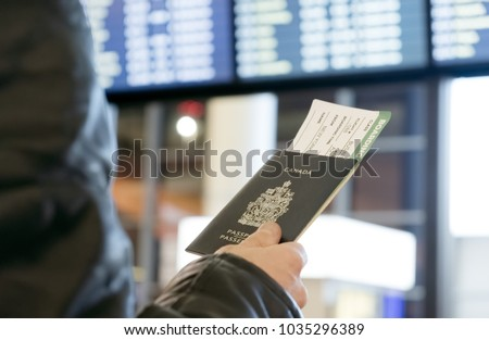 A man with a Canadian passport and boarding pass looks at the airport departure