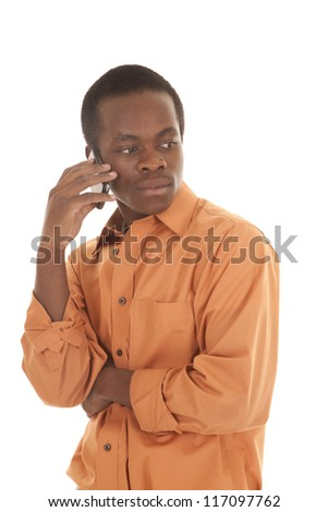 A man with a cell phone up to his ear listening with a serious expression on his face,