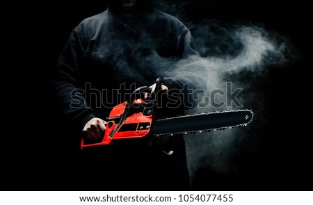 A man with a chainsaw in his hands close up against the background of smoke.