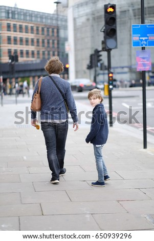 A man with a child on a city street. London, Great Britain. #650939296