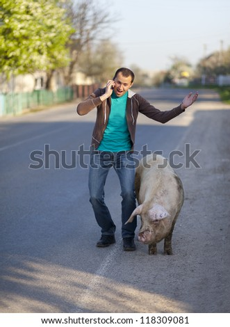 A man with a dirty pig is on the cellphone