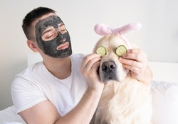 A man with a dog takes care of facial skin at home. A guy and a golden retriever put on a clay face mask. The concept of male health and beauty, cosmetology, body and skin care.