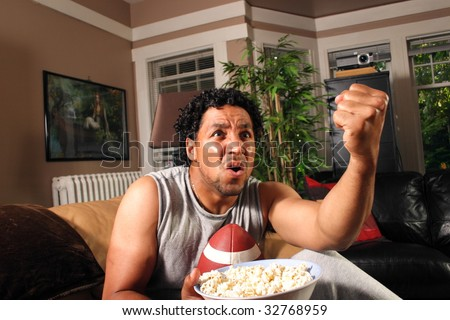A man with a football and popcorn shakes his fist at the TV