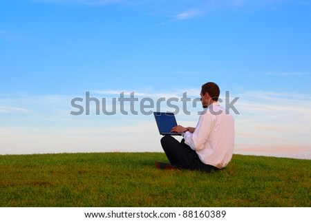 A Man with a Laptop siting on a green meadow