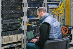 A man with a laptop sits in a server room. A technician works near the racks of a modern data center. The system administrator configures the computer hardware.