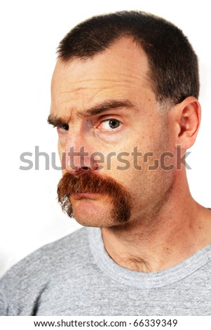 a man with a large mustache looks at the viewer and raises one eyebrow