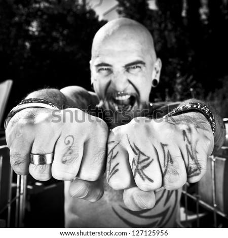 A man with a lot of tattoos at a junkyard
