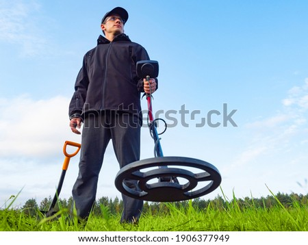 A man with a metal detector and a shovel is photographed from below. Treasure hunter with metal detector. A man is looking for treasure. Person with a metal detector against a blue sky. Stockfoto ©