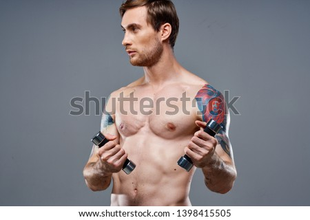 a man with a muscled muscular torso dumbbells in the hands of a tattoo muscles training