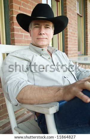 A man with a peaceful relaxed posture, sitting in a rocker on a porch, wearing a cowboy hat.
