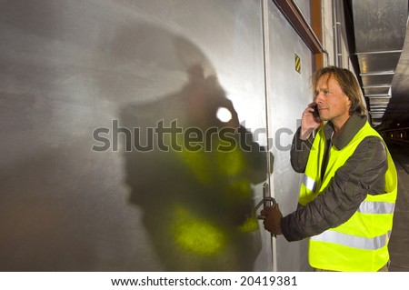A man with a phone in his hand wearing a yellow reflective safety vest opening a steel door inside a tunnel - stock photo