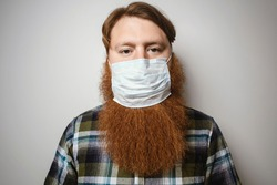 A man with a red hair and a red beard wearing a face mask.  A bearded man with a face mask protecting himself from virus epidemic and  other diseases.
