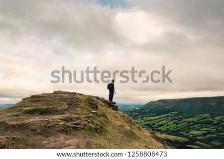 A man with a rucksack looking across the landscape of fields and hills from the top of a hill on the English, Welsh border. Black Mountains, Wales.