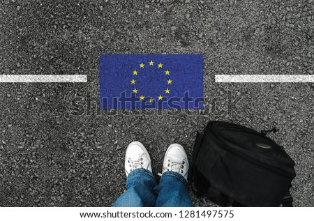 a man with a shoes and backpack is standing on asphalt next to flag of European Union and border