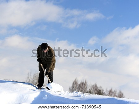 A man with a shovel removing snow from a driveway