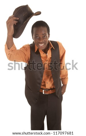 A man with a smile on his face taking off his cowboy hat