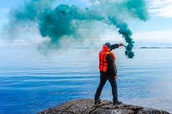 A man with a smoke torch. The rescue. Distress call. The man lights a smoke signal. A man in a life jacket. SOS. signal by smoke.