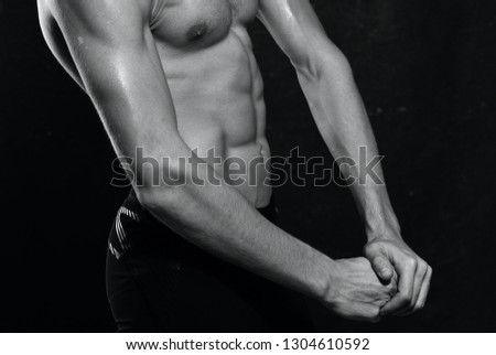 A man with a strong torso and strong arms against a dark background               #1304610592