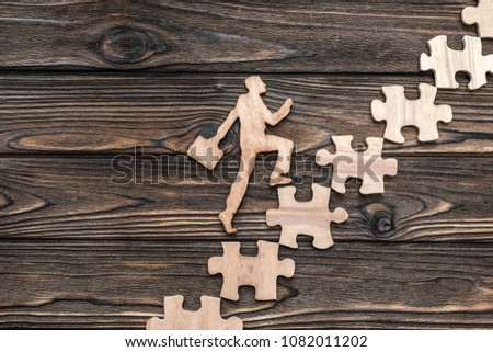 a man with a suitcase climbs the ladder from puzzles on a wooden background. career. business. finance.