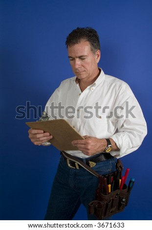 A man with a toolbelt around this waist looking at something on a clipboard.