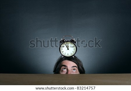 A man with an alarm clock on his head on a dark background.