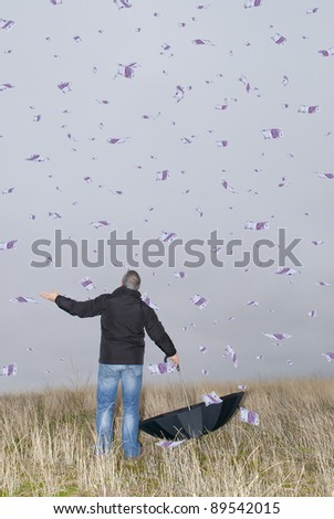 A man with an umbrella in the field amid a storm of money.