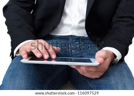 A Man with blue jeans working on a tablet pc with he's hand