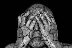 A man with cracking skin covering his eye with his hand for the concept: Deteriorating Blind Justice.