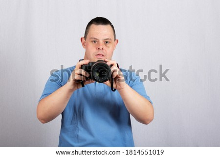 a man with down syndrome with camera on white background Stock photo ©