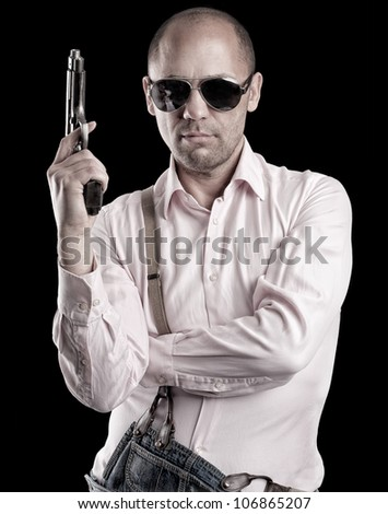 A man with glasses holding a gun.