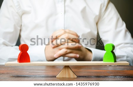 A man with hands in the lock and looks at the scales with green and red figures. conflict resolution and search for a compromise. Disagreement and misunderstanding, establishing contact. Agreements