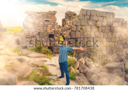 A man with hands spread out towards the sun in the  medieval abandoned ruins. Mystic fog in the background. Toned #781708438