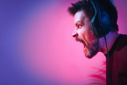 A man with headphones is shouting. A man plays computer games at home. The guy is watching a video with headphones. An emotional player. The irritated man lost. Neon light.