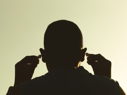 A man with his back turned to headphones The hand is holding the bluetooth earphone on both sides With a sky background