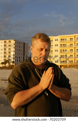A man with his eyes closed praying at the beach with hotels behind him.