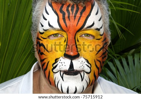 A man with his face painted as a tiger with tropical leaves in the background.