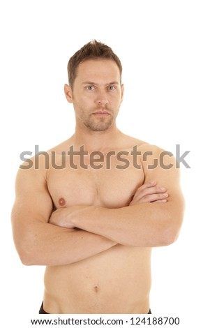A man with no shirt on and arms folded with a serious expression on his face