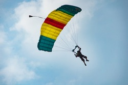 A man with parachute floating in the sky