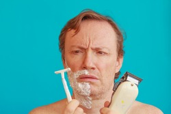 a man with shaving -foam about to shave but is undecided whether to choose razor or razor-blade