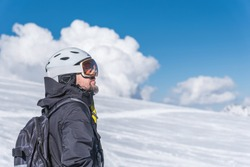A man with skis stands high in the mountains enjoying the scenery. Go downhill skiing, extreme relaxation
