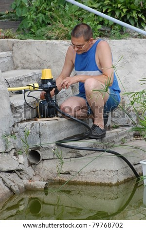 A man with the electric water pump for watering garden near pond.Near Kiev,Ukraine
