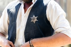 A man with the star shaped sheriff badge in his vest. Wild west justice officer and lawman