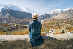 A man with traditional dress sitting on wall and looking at Hunza valley in autumn season, Gilgit Baltistan in Pakistan, Asia