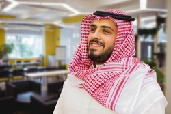 A man with traditional Saudi dress , standing on office background. image