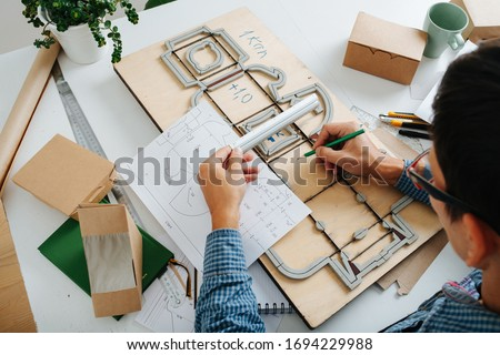 A man work on the table with drawings, rulers and pencils, ready-made boxes and punching platen Stockfoto ©