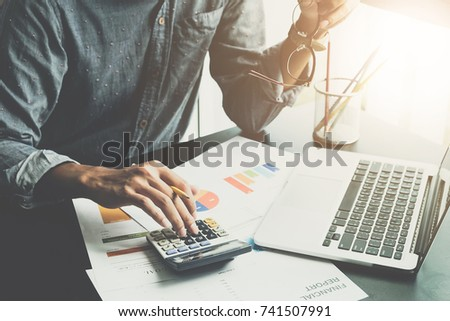 A man working about financial and analysis business document with calculator and holding glasses at his office to calculating expenses, Accounting concept