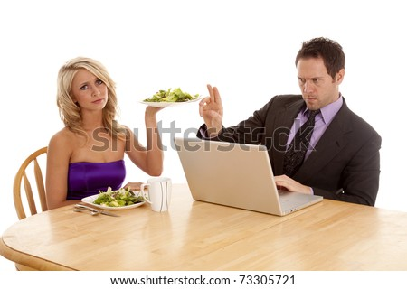 a man working on his computer the woman is trying to give him a salad to eat and he tells her with his hand to wait a minute.