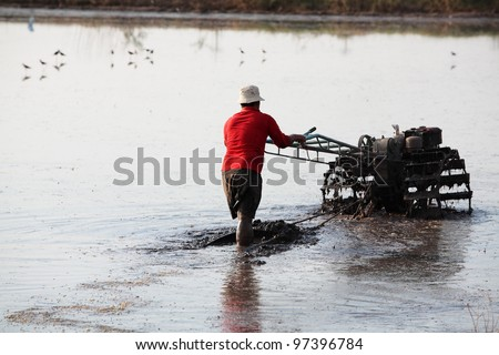 A man working with a handheld motor plow in a rice field from Thailand