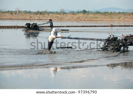 A man working with a handheld motor plow in a rice field from Thailand - stock photo